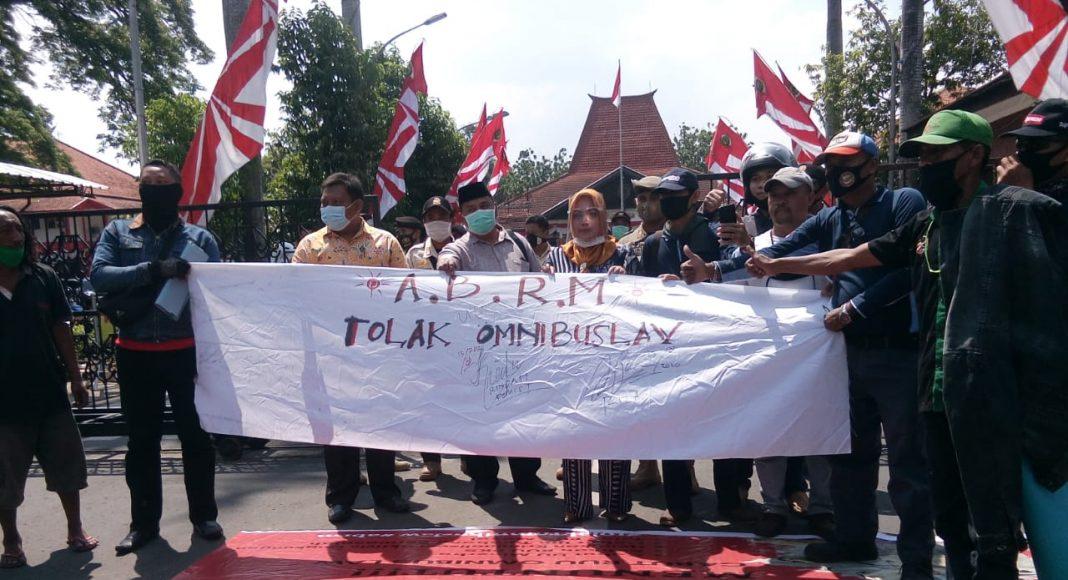 Ratusan massa yang terdiri dari LSM GMBI, HMI Mojokerto, BPJS Wact, KASBI Mojokerto, BEM Mojokerto, yang tergabung dalam Aliansi Buruh dan Masyarakat Mojokerto (ABRM) mendatangi gedung Pemerintah Kabupaten Mojokerto, pada Kamis (13/08).