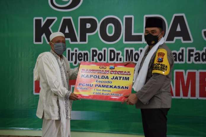 Saat Kapolda Jatim Irjen Pol Muhammad Fadil Imron menyerahkan bantuan ke warga terdampak Covid-19 melalui PCNU Pamekasan. (Foto: Beritabaru.co/Arif Billah)