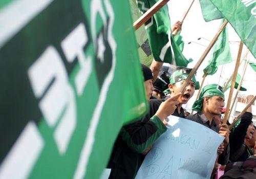 Puluhan anggota Himpunan Mahasiswa Islam (HMI) mengibarkan bendera/FOTO ANTARA/Irwansyah Putra.