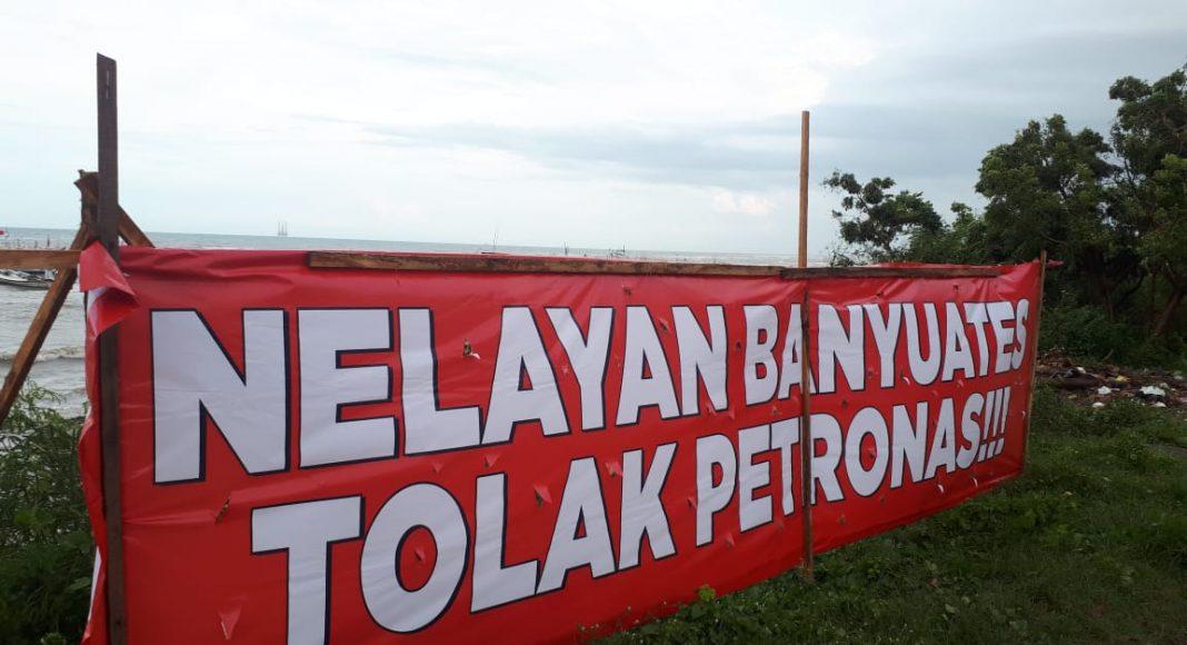 Nelayan Banyuates bentangkan sepanduk penolakan pertambang minyak dan gas oleh Petronas. (Foto: Beritabaru.co/ Ulfatus Soimah)