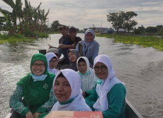 Naik perahu, PAC Fatayat dan PAC IPPNU Kalitengah terjang banjir bagikan puluhan paket sembako.